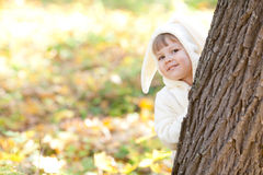 Little girl in costume bunny in the autumn forest Stock Images