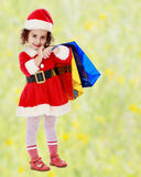 Little girl in costume of Santa Claus with colorful packages Royalty Free Stock Photography