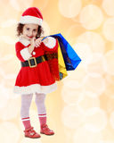 Little girl in costume of Santa Claus with colorful packages Royalty Free Stock Images