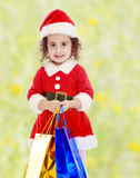 Little girl in costume of Santa Claus with colorful packages Stock Photo