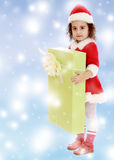 Little girl in costume of Santa Claus with gift Stock Photography