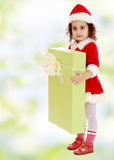 Little girl in costume of Santa Claus with gift Royalty Free Stock Photos