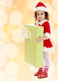 Little girl in costume of Santa Claus with gift Royalty Free Stock Photography