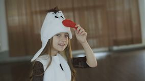 Little girl in costume of snow girl posing at camera. In hall. Full HD stock video footage