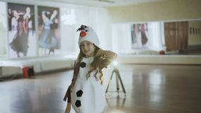 Little girl in costume of snow girl posing at camera. In hall. Full HD stock video