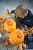 Little girl in a costume of a witch sitting near two pumpkins, v Royalty Free Stock Photos