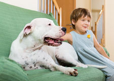 Little girl on couch with dog Stock Image