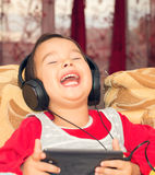 Little girl on the couch with earphones Royalty Free Stock Photography