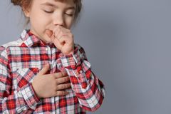 Little girl coughing on   background. Little girl coughing on grey background Stock Image
