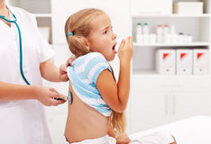 Little girl coughing at the doctor Stock Images