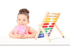 Little girl counting her savings on an abacus Stock Image