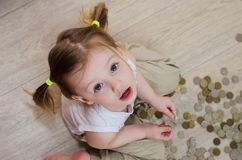 Little girl counting with coins. Little girl counting and playing with coins royalty free stock images