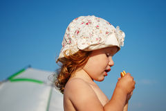 Little girl covered in crumbs eats cookies on the beach Royalty Free Stock Photography