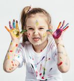 Little girl covered in paint making funny faces. Kindergarten kid. Prankster Stock Images