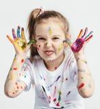 Little girl covered in paint making funny faces. Kindergarten kid. Prankster stock images