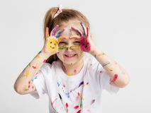 Little girl covered in paint making funny faces. Creative fun. Childhood stock images