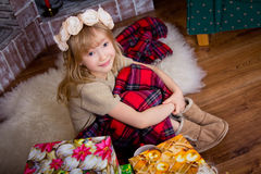 The little girl covered by a plaid is sitting at a fireplace and Royalty Free Stock Photo
