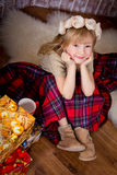 The little girl covered by a plaid  is sitting near  Christmas g Royalty Free Stock Photography