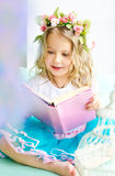 Little girl covered with wreath reading book Stock Photography