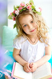 Little girl covered with wreath reading book Stock Photo