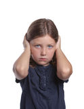 Little Girl Covering Ears. A cute little girl with big blue eyes covers her ears while making a sad face Royalty Free Stock Images