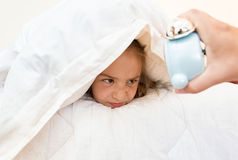 Little girl covering head with pillow and looking at alarm clock Stock Image