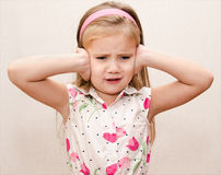 Little girl covering her ears. Disappointed little girl covering her ears Stock Photos