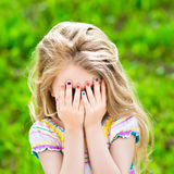 Little girl covering her eyes with her hands Stock Photo