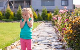Little girl covering her face, does not want be Stock Image