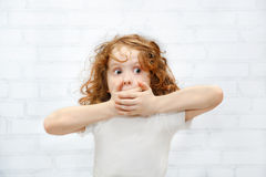 Little girl covering her mouth with her hands. Surprised or scar Stock Photography