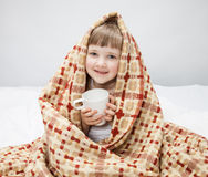 Little girl covering with a rug and holding a cup Royalty Free Stock Photography