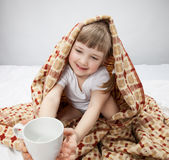 Little girl covering with a rug and holding a white cup Royalty Free Stock Photo