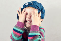 Little girl covers  face with her  hands. Isolated on gray Stock Photo