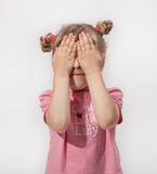 Little girl covers her face with her hands. White background Royalty Free Stock Image