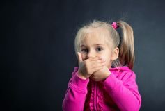 Little girl covers her mouth with hands. On dark background royalty free stock photography