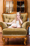 Little girl covers her mouth with hands in home.  stock photos