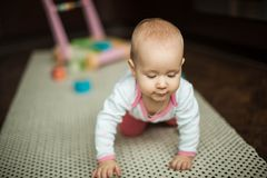 Little girl crawling on the floor on the carpet at home stock photos
