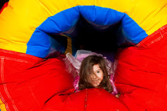 Little Girl Crawling Through Inflatable. A little girl crawls through a bouncy inflatable with a big smile on her face Royalty Free Stock Images