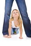 Little girl crawls between mom legs Stock Images