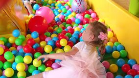 Little girl is crawls in pool with plastic balls. stock video