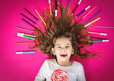 Little girl with crayons and lollipop. royalty free stock photography
