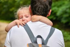 A little girl cries and hugs father. A little girl cries and hugs her father stock images