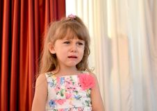 The little girl cries in the kindergarten hall stock images