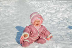 The little girl cries sitting on snow Stock Photo