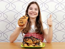 Little girl with croissants and thumb up Royalty Free Stock Photo