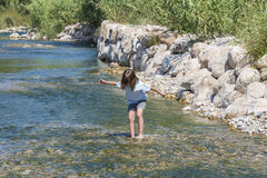 Little girl crossing a river Royalty Free Stock Photos