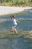 Little girl crossing a river Stock Images