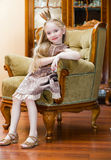 Little girl with crown. On chair Royalty Free Stock Image