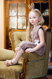 Little girl with crown. On chair Royalty Free Stock Photos