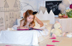 A little girl with a crown on her head laying on a bed and reading a book Stock Photography
